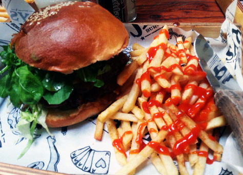 The cheese, rocket and caramelised onion topped 'Jerry' burger at Jerry's, with fries doused in Sriracha sauce.