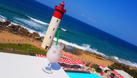 The CL2 cocktail (coconut milk, lavender and litchi) with stunning striped sea and sky beyond, as well as iconic red-and-white lighthouse and Oyster Box Hotel striped pool umbrellas. Love!