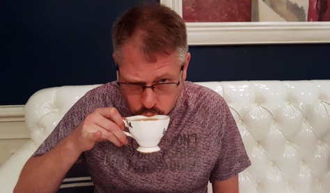 Husband, caught sipping tea with pinkie finger extended.